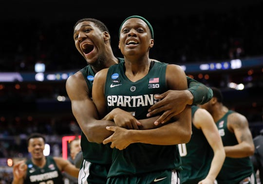 Michigan State guard Cassius Winston (5) is hugged by teammate forward Aaron Henry (11) after defeating Duke in an NCAA men's East Regional final college basketball game.