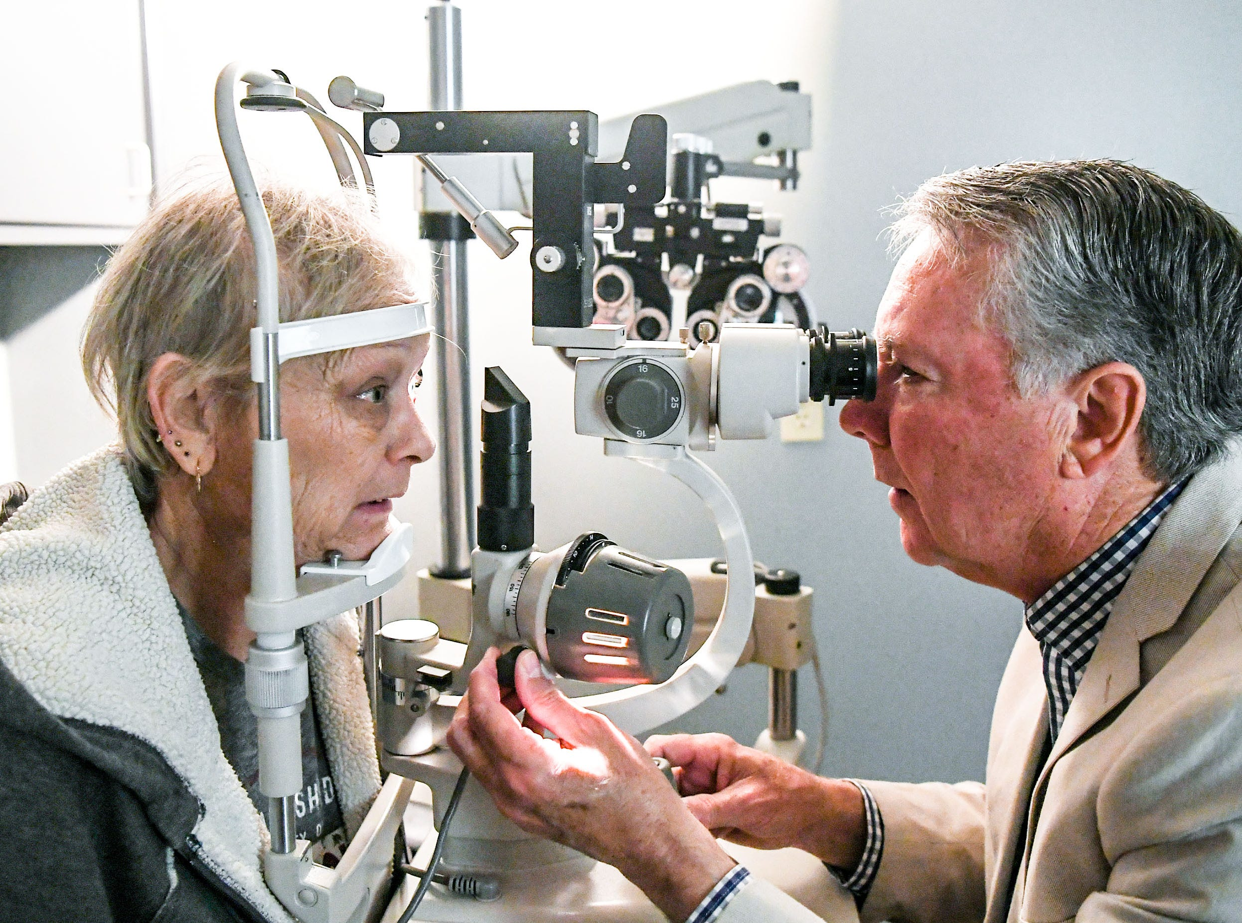 Dr. Jim Chamberlain, left, checks the vision of patient Jackie Howard of Anderson, the first to get vision care at the Anderson Free Clinic in Anderson Tuesday. The free clinic, open since 1984, recently added dental to the medical and pharmacy, and now has vision care.