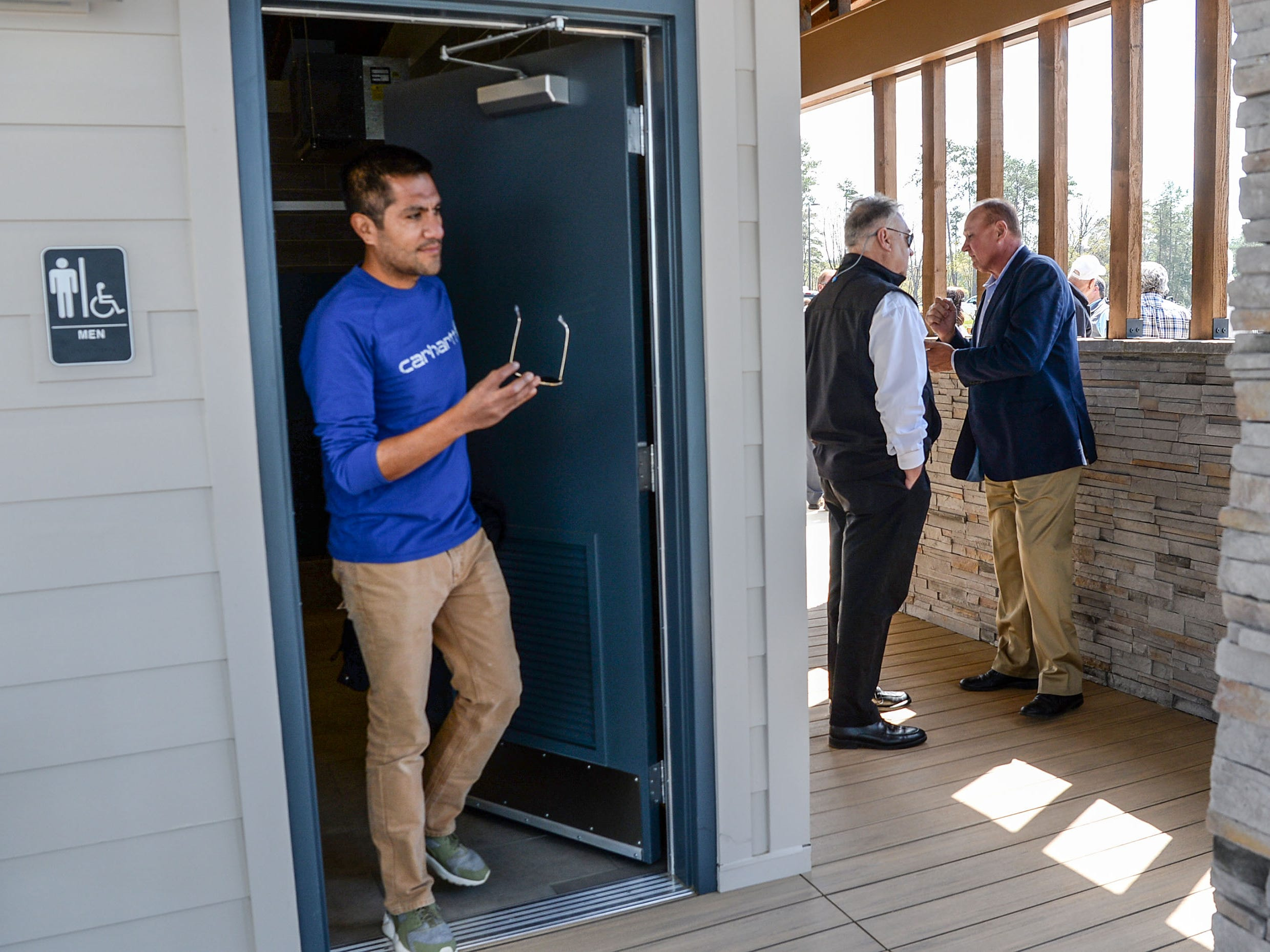 Eric Lopez, left, BASSMASTER director of operations, checks out the newly opened bathroom near Rusty Burns, middle, Anderson County Administrator, and Tommy Dunn, right, Anderson County Council chairman, after the Green Pond Landing & Event Center Facilities ribbon cutting event in Anderson Tuesday.