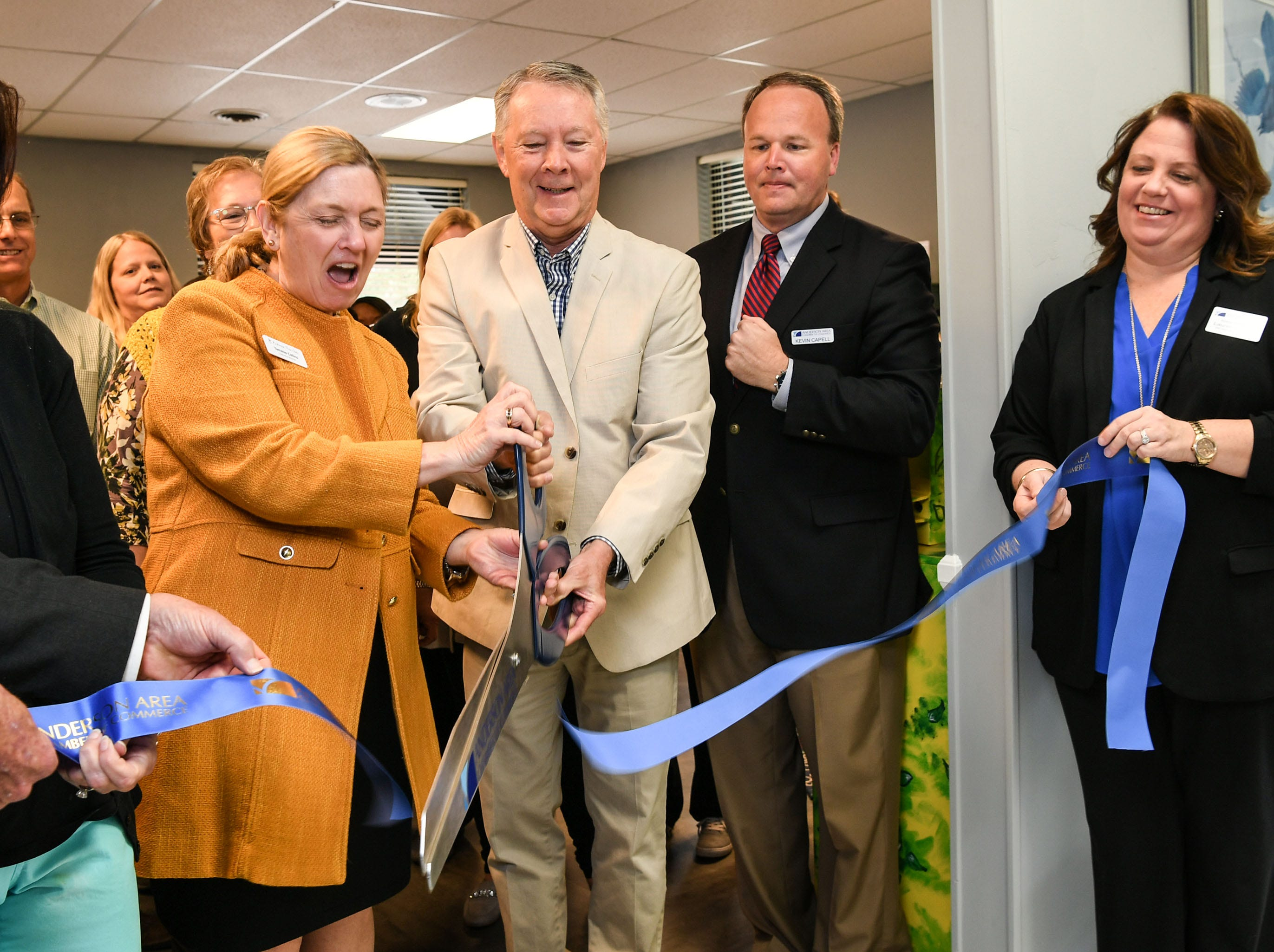 Tammie Collins, left, executive director of the Anderson Free Clinic, cuts a ribbon with vision clinic Dr. Jim Chamberlain, at the clinic in Anderson Tuesday. The free clinic, open since 1984, recently added dental to the medical and pharmacy, and now has vision care.
