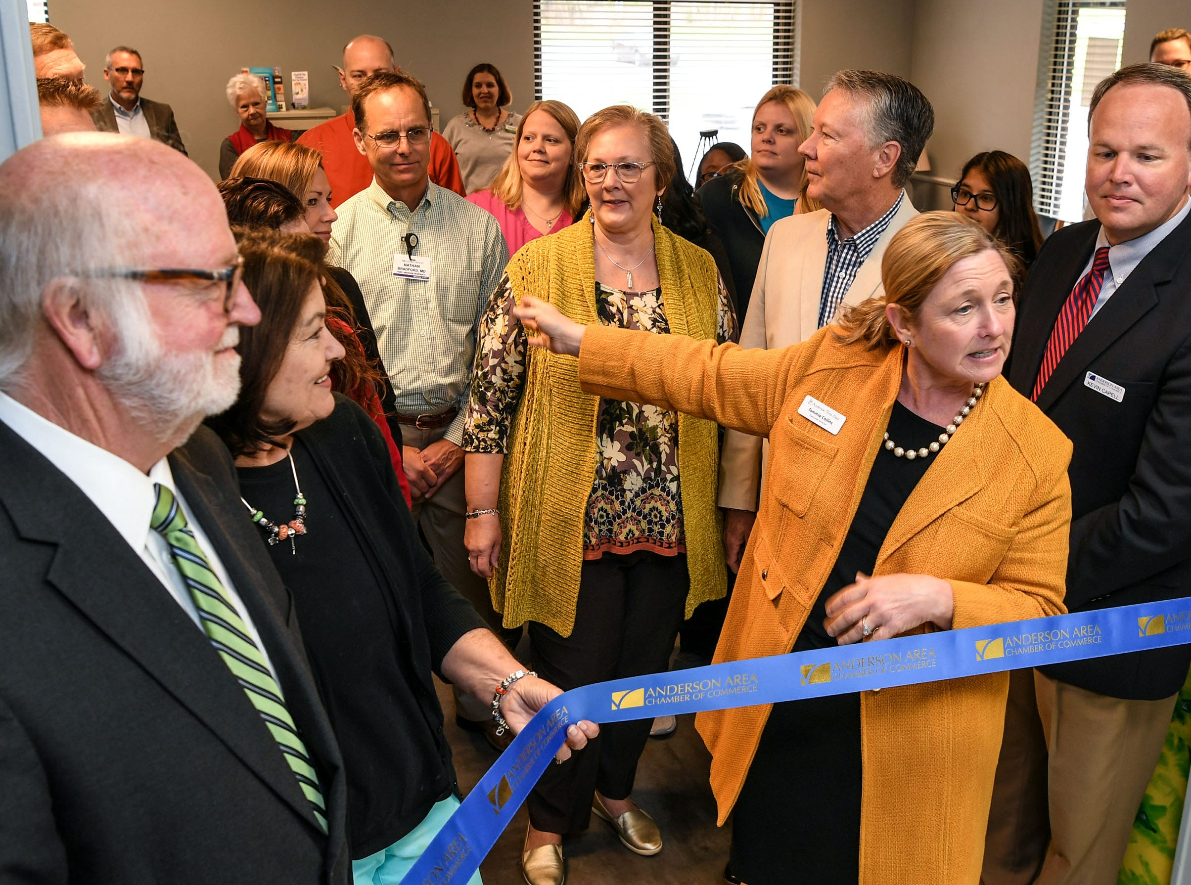 Tammie Collins, middle, executive director of the Anderson Free Clinic, gets ready to cut a ribbon with Hugh and Rita Burgess, left, and Vice President Kevin Capell, right, at the clinic in Anderson Tuesday. The free clinic, open since 1984, recently added dental to the medical and pharmacy, and now has vision care.