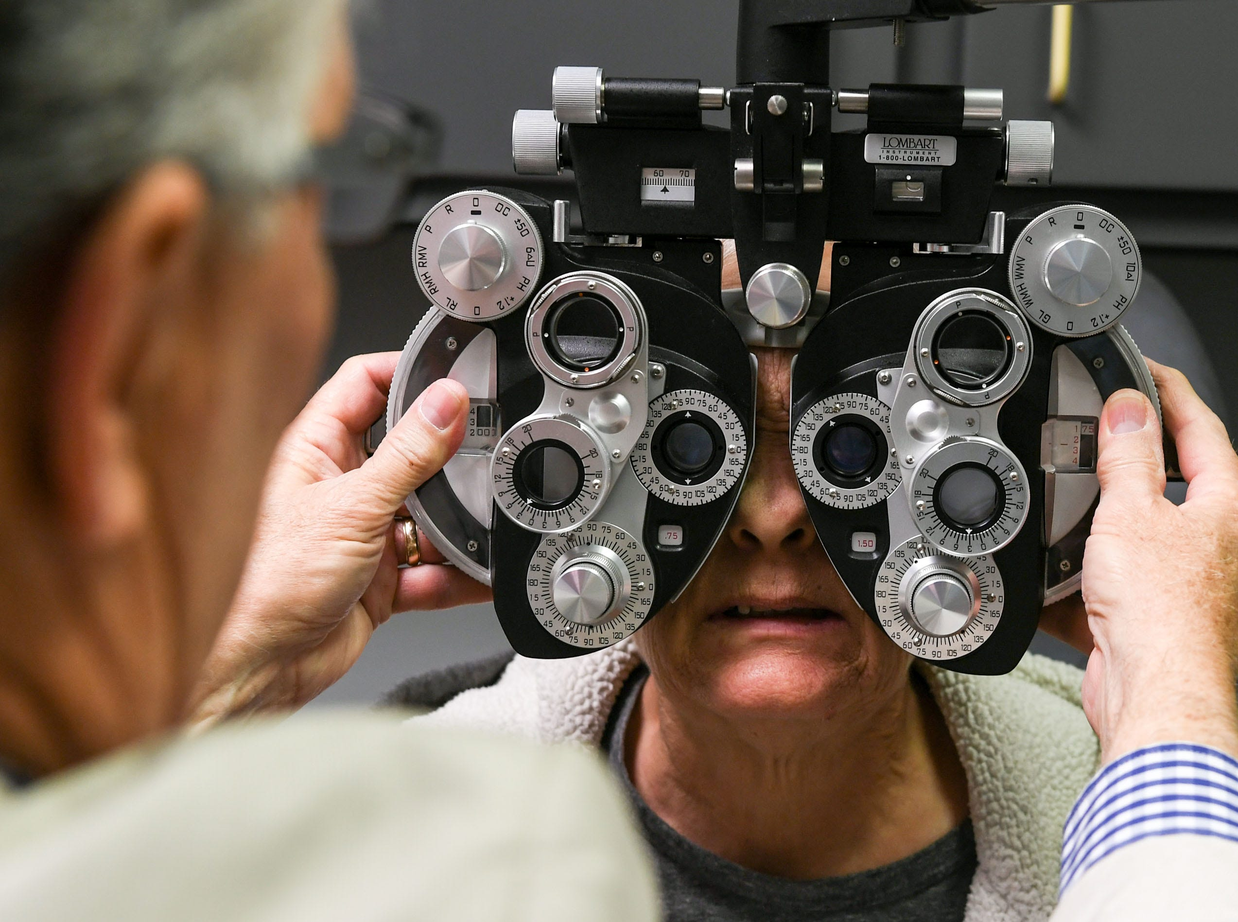Dr. Jim Chamberlain, left, uses a phoropter as one of several tests to check the vision of patient Jackie Howard of Anderson, the first to get vision care at the Anderson Free Clinic in Anderson Tuesday. The free clinic, open since 1984, recently added dental to the medical and pharmacy, and now has vision care.