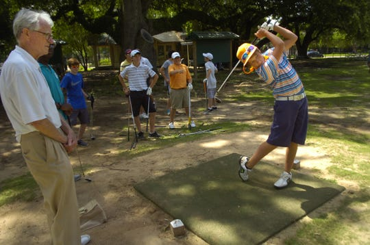 Scott Brame (left), watches participants in a golf camp at Bringhurst Golf Course in 2013. The city of Alexandria is placing a memorial on the course to Brame, who passed away in April, in recognition of his efforts to keep the historic golf course from closing a few years ago.