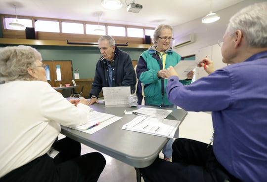 Dave and Jan Paul, center, recieve their ballots as voters head to the polls at Peace Lutheran Church on Tuesday, April 2, 2019, in Neenah, Wis.