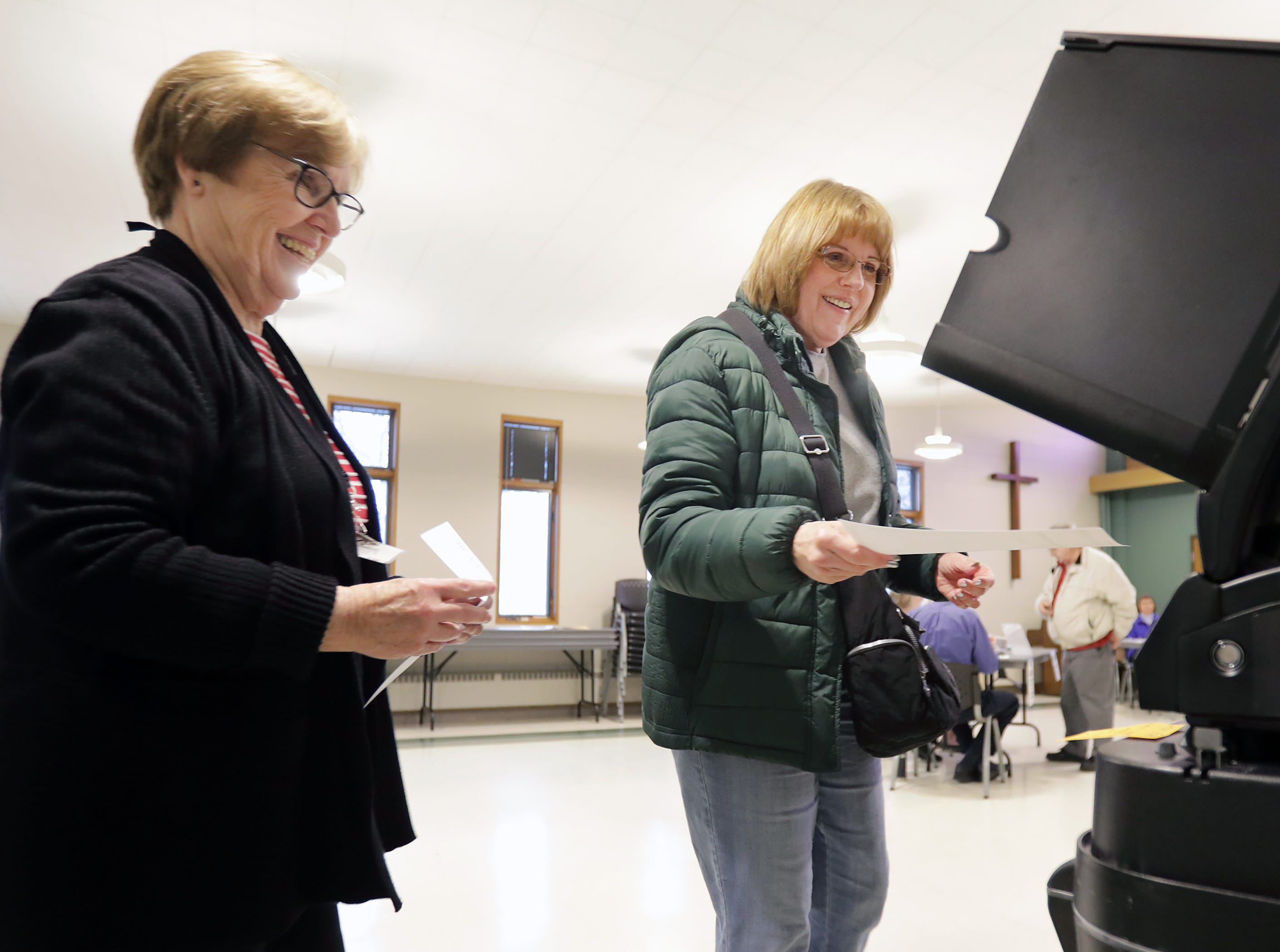Poll worker Terri Wasco, left, helps Cheryl Pagel submit her ballot as voters head to the polls at Peace Lutheran Church on Tuesday, April 2, 2019, in Neenah, Wis.