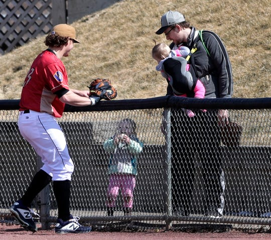 The Wisconsin Timber Rattlers' pitcher #23 Scotty Sunitsch hands a ball to a fan during Fan Fest at Neuroscience Group Field at Fox Cities Stadium on Tuesday, April 2, 2019, in Grand Chute, Wis.