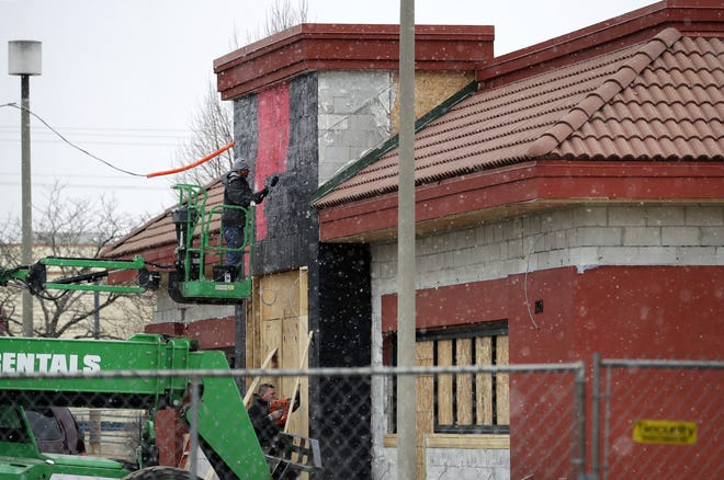 Despite flurries, workers continue to transform the former Bucca di Beppo into P.F. Chang's in Grand Chute.
