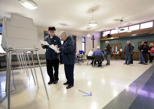 Jim and Dorothy Francart look over their ballots before filling them out Tuesday at Peace Lutheran Church in Neenah.