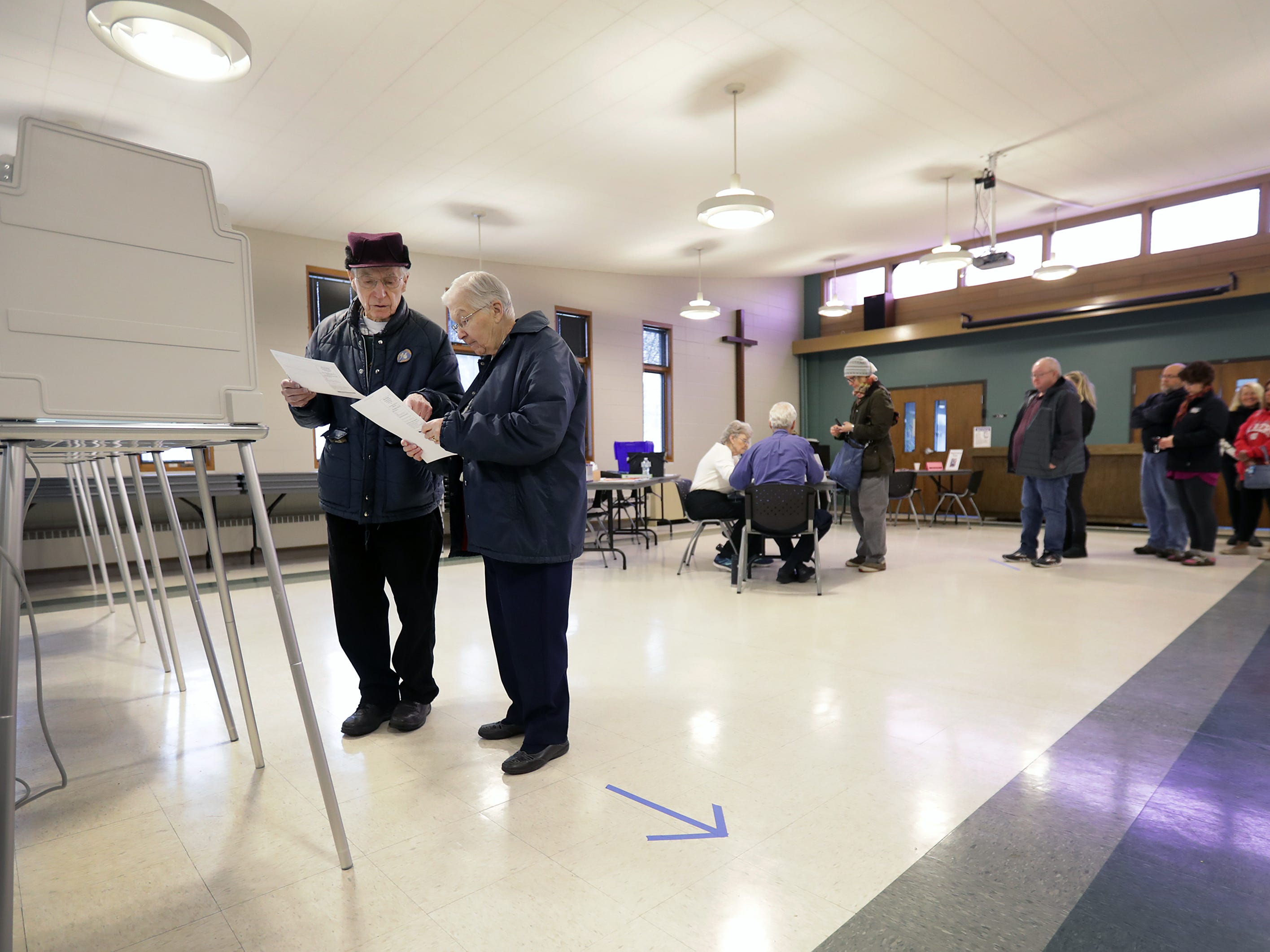 Jim and Dorothy Francart look over their ballots before filling them out as voters head to the polls at Peace Lutheran Church on Tuesday, April 2, 2019, in Neenah, Wis.