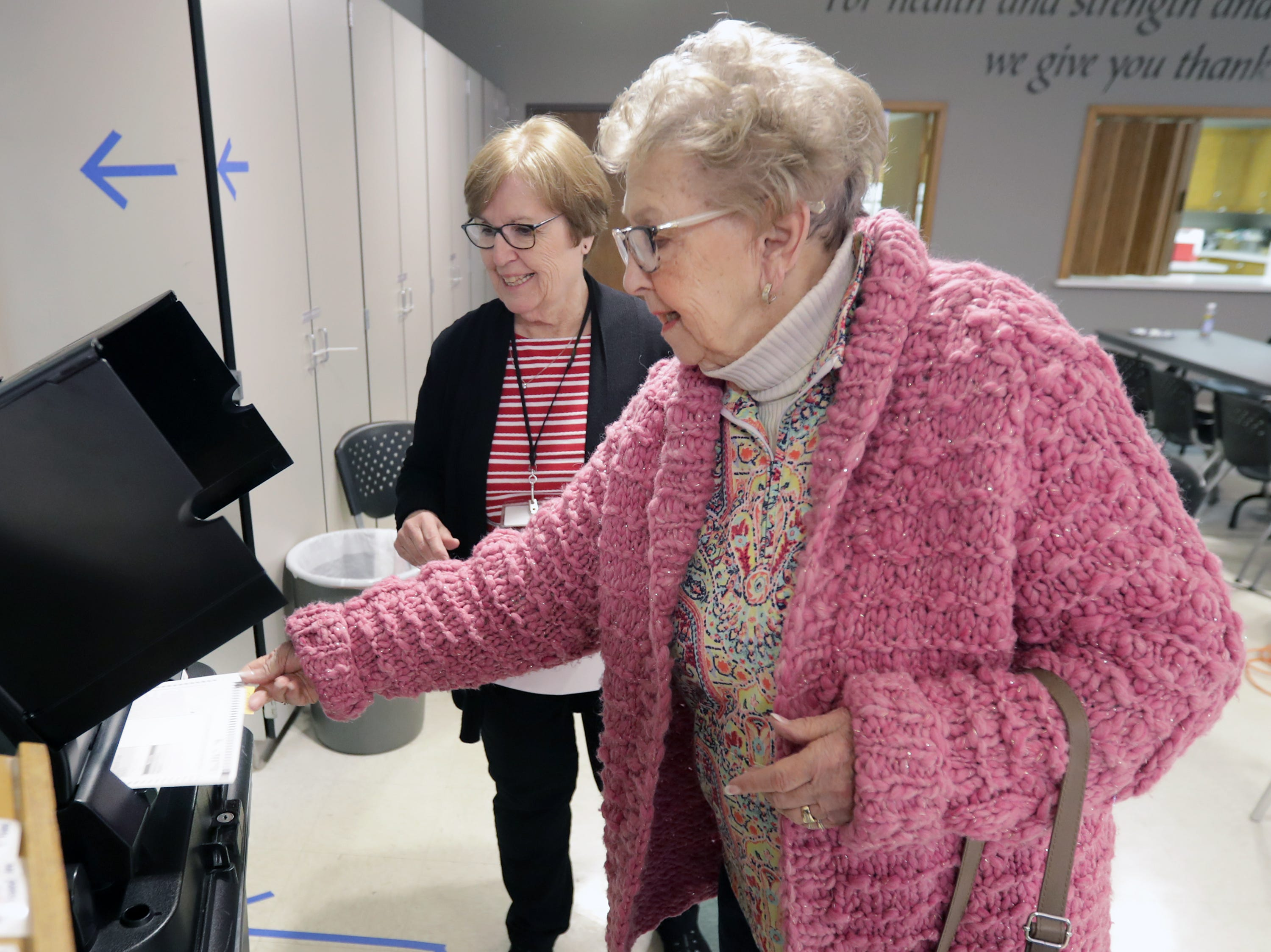 Poll worker Terri Wasco, left, watches Mary Piette submit her ballot as voters head to the polls at Peace Lutheran Church on Tuesday, April 2, 2019, in Neenah, Wis.
