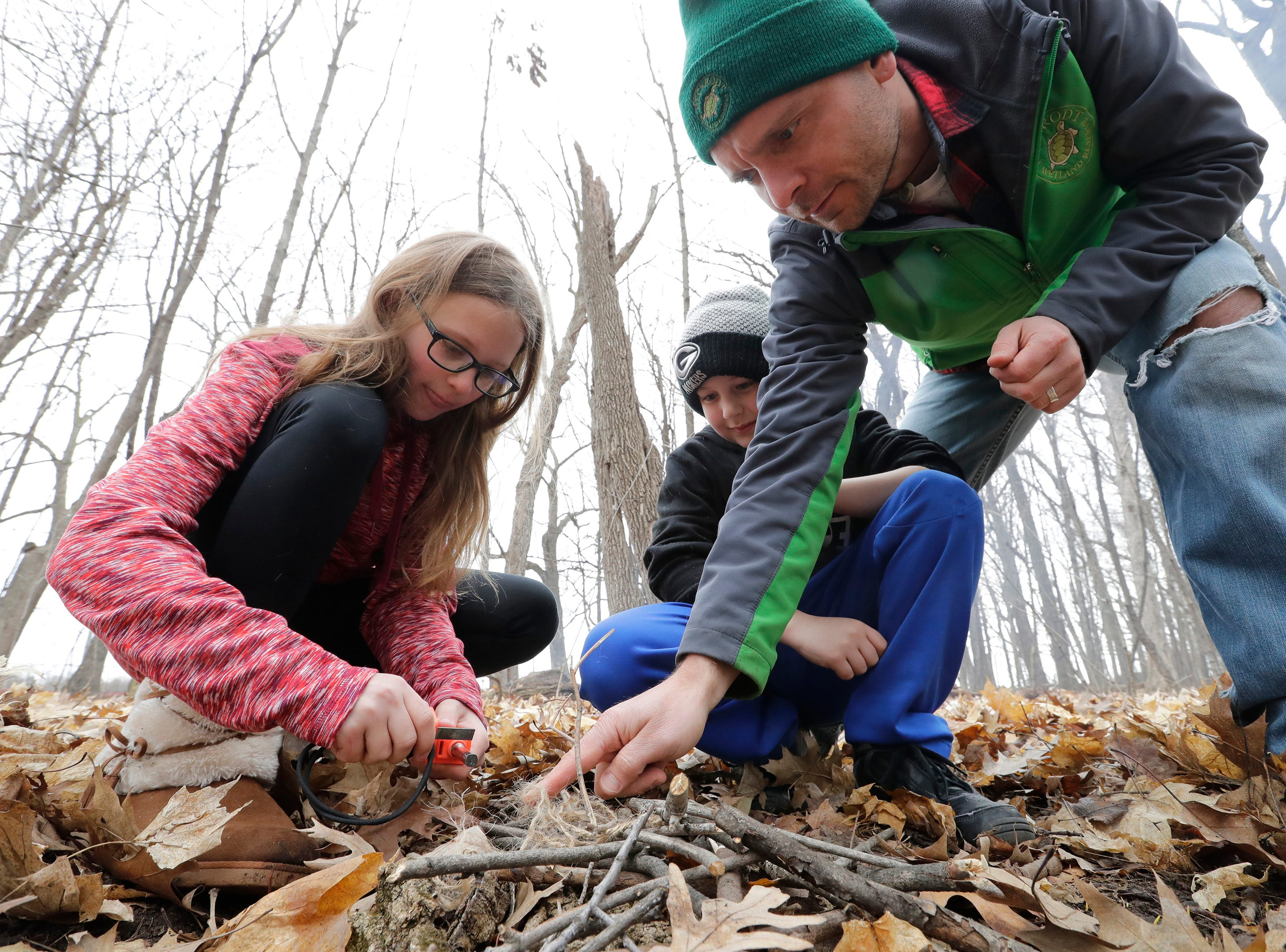 Ivy Ebel, 11, left, and Vincent Thiel, 8, learn how to build a fire in the wilderness with the assistance of Luke Schiller, director of education at Heckrodt Wetland Reserve, Thursday, March 28, 2019, at Memorial Park in Neenah, Wis. Heckrodt Wetland Reserve partnered with the Neenah Park and Recreation department to teach kids how to build shelters and fires outside during this one day event.Dan Powers/USA TODAY NETWORK-Wisconsin
