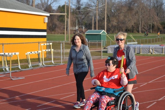 Marianne Reagan (right) pushes daughter Kelly Reagan as Rae Ellen Mandelbaum (left) accompany them at Monmouth Regional's track.