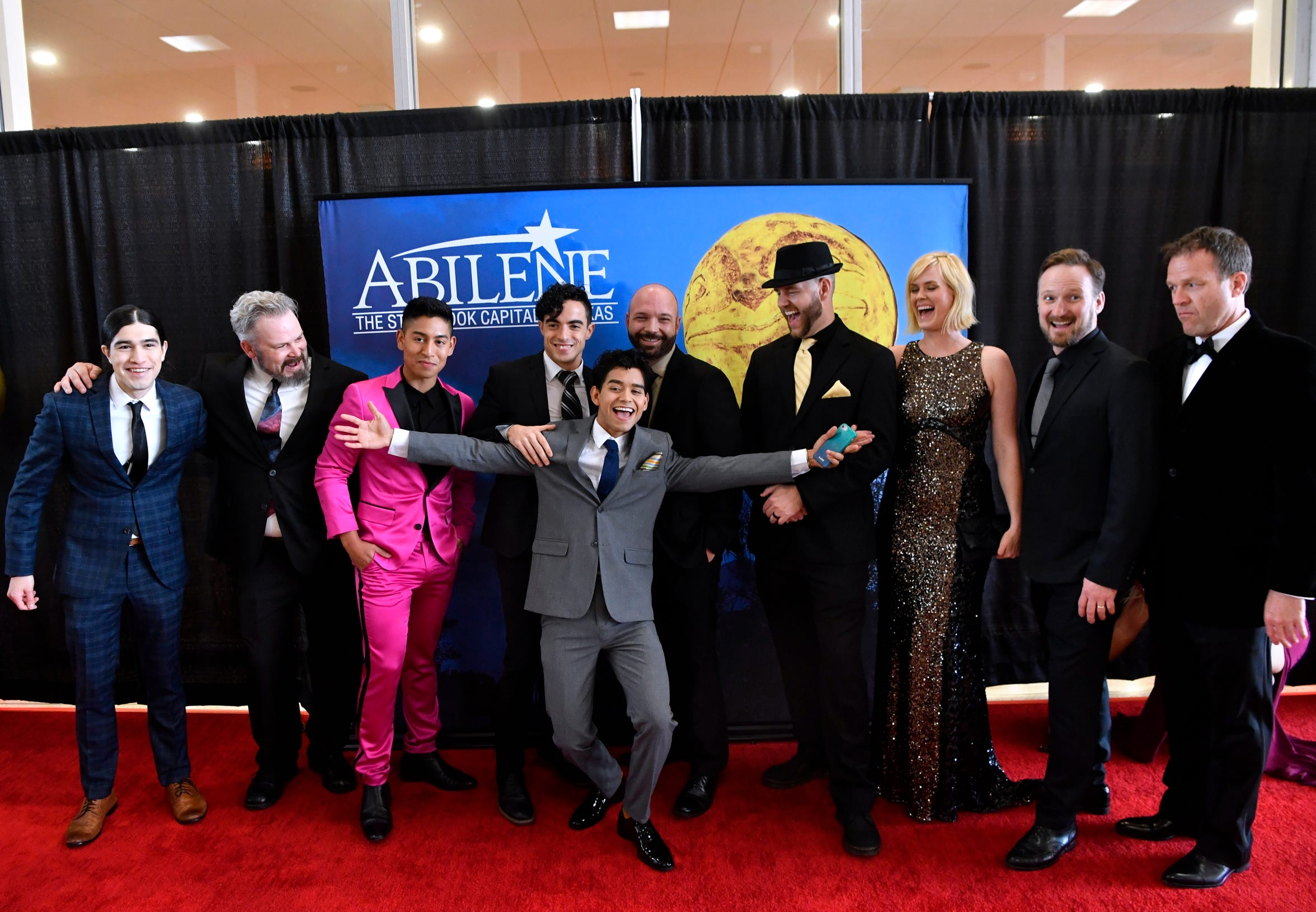 """Germain Arroyo spreads his arms wide for a group photo of """"Brother's Keeper"""" cast and crew at the movie's premiere March 30. Behind his left hand is director Todd Randall and co-star Abigail Hawk. The film follows the 2009 Abilene High School Eagles championship football season."""