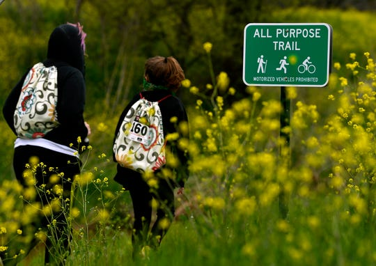 Hikers walk past mustard flowers during the Mayor's Hike along Cedar Creek Saturday. At least 100 people, made up of friends and families with some individuals as well, came out for the three-mile walk despite blustery conditions that morning.
