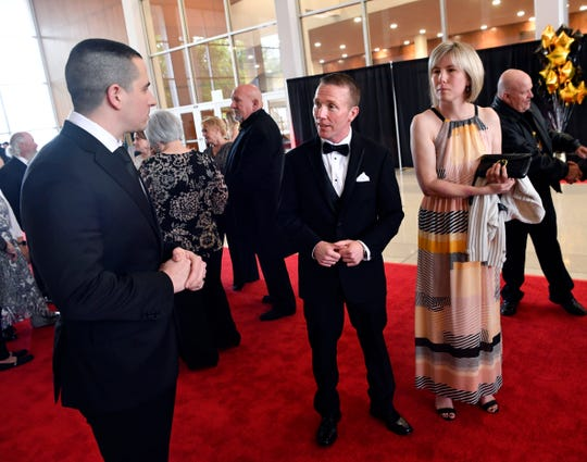 """Oliver Brooks, a wide receiver on the 2009 Abilene High School Eagles, speaks with Phil Sage and his wife, Michelle, before the premiere of """"Brother's Keeper,"""" a film based on the Eagle's championship season that year."""