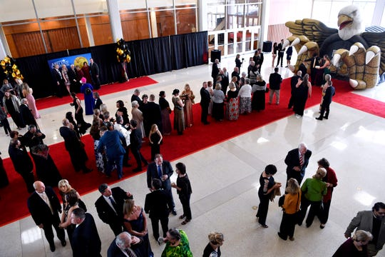 Attendees line up on a red carpet to be photographed in front of the Abilene High School inflatable Saturday.