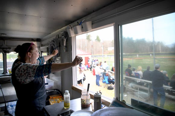 Cecilia Marchesini cheers from the Cecilia's Kitchen food truck during an Asheville High School home baseball game on March 29, 2019. Marchesini says that she loves the game of baseball and finds it endlessly exciting.
