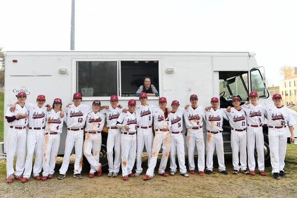 The Asheville High School Cougar baseball team poses with Cecilia Marchesini and her Cecilia's Kitchen food truck after a home game on March 29, 2019. The team often get treats after the game. On March 29 Marchesini made the team cupcakes.