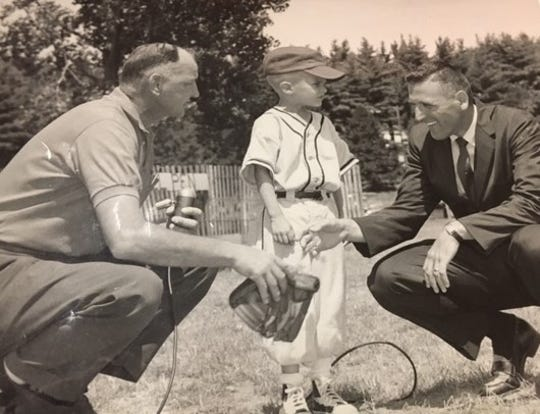 The inventor of T-Ball Jerry Sacharski, left, talks to MSU's Gus Ganakas and young T-Ball player Melvin Mills during the production of a special film on the campus to educate people about the 'new' sport of T-Ball in 1960.