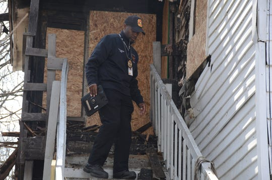 Fire Marshal Quincy Jones climbs down an outside stairway from an apartment at 513 Hamblin Ave.
