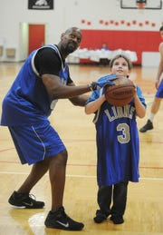 John Stormzand | Staff Photographer Mason Muer of Grosse Pointe Park takes some pointers on his free throws from former Detroit Lions wide receiver Herman Moore.