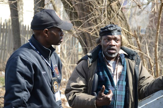 Fire Marshal Quincy Jones, left, talks Tuesday with resident  Jeff Martin, 50, Tuesday about the fire which destroyed an apartment house on Sunday.