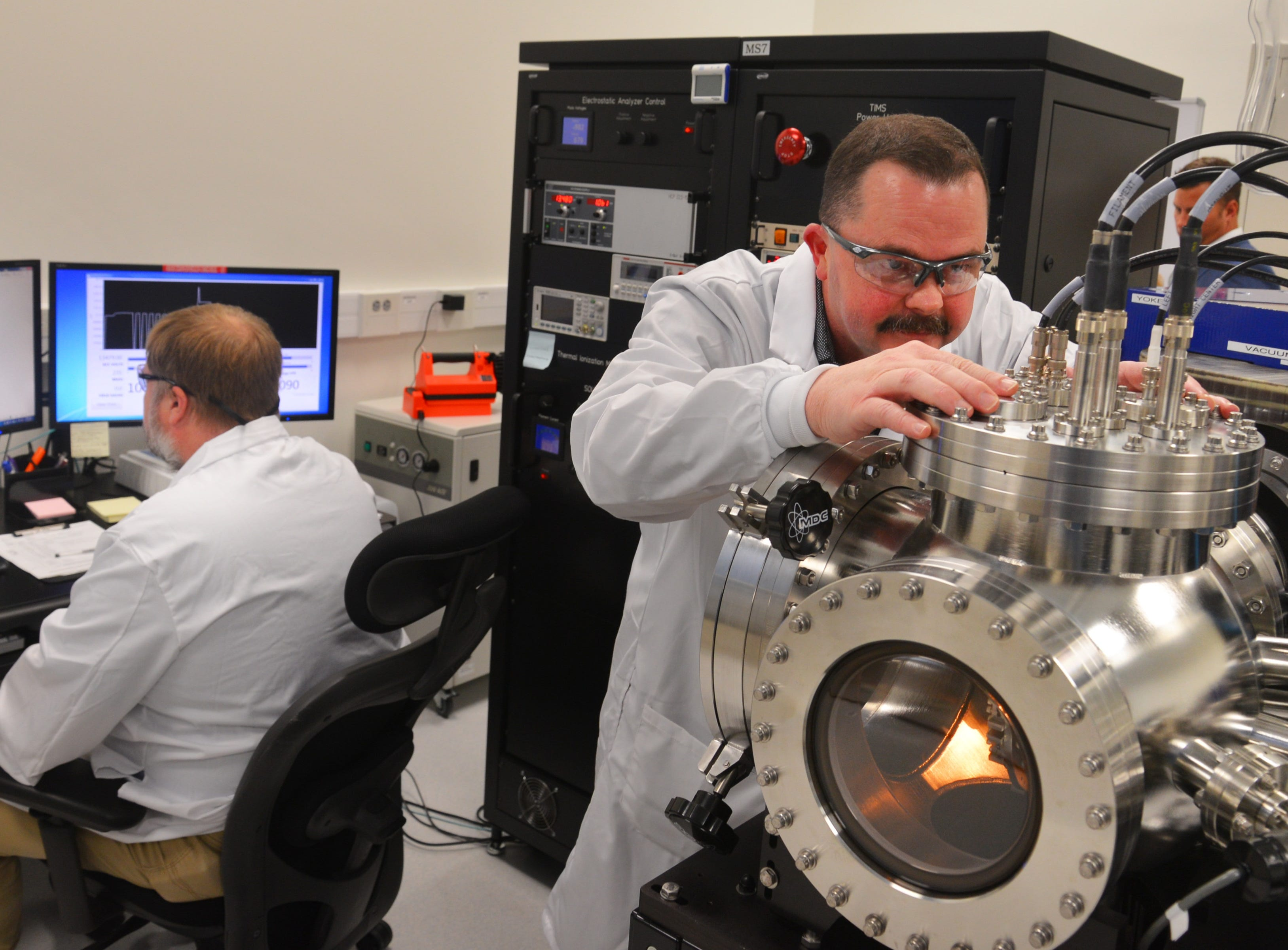 Wesley Schuler (right), flight chief for mass spectrometry, and Jason Webb, mass spectrometry technician, analyze uranium and plutonium isotopes inside an AFTAC laboratory.