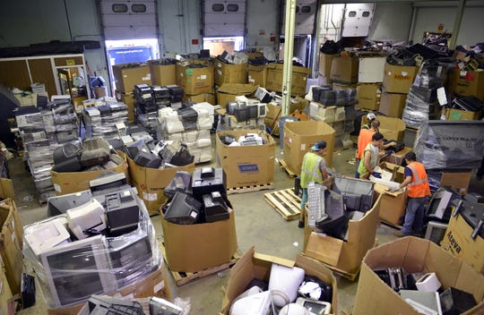 Workers sort electronic equipment at Good Point Recycling in Middlebury, Vt., on Aug. 30, 2013.