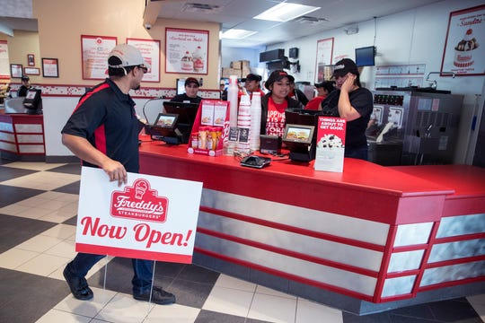 Anthony Lopez, a supervisor at Freddy's Frozen Custard & Steakburgers, prepares to put out signs announcing the burger and custard shop is open on Tuesday, April 2, 2019. There was a line before the new burger joint opened.
