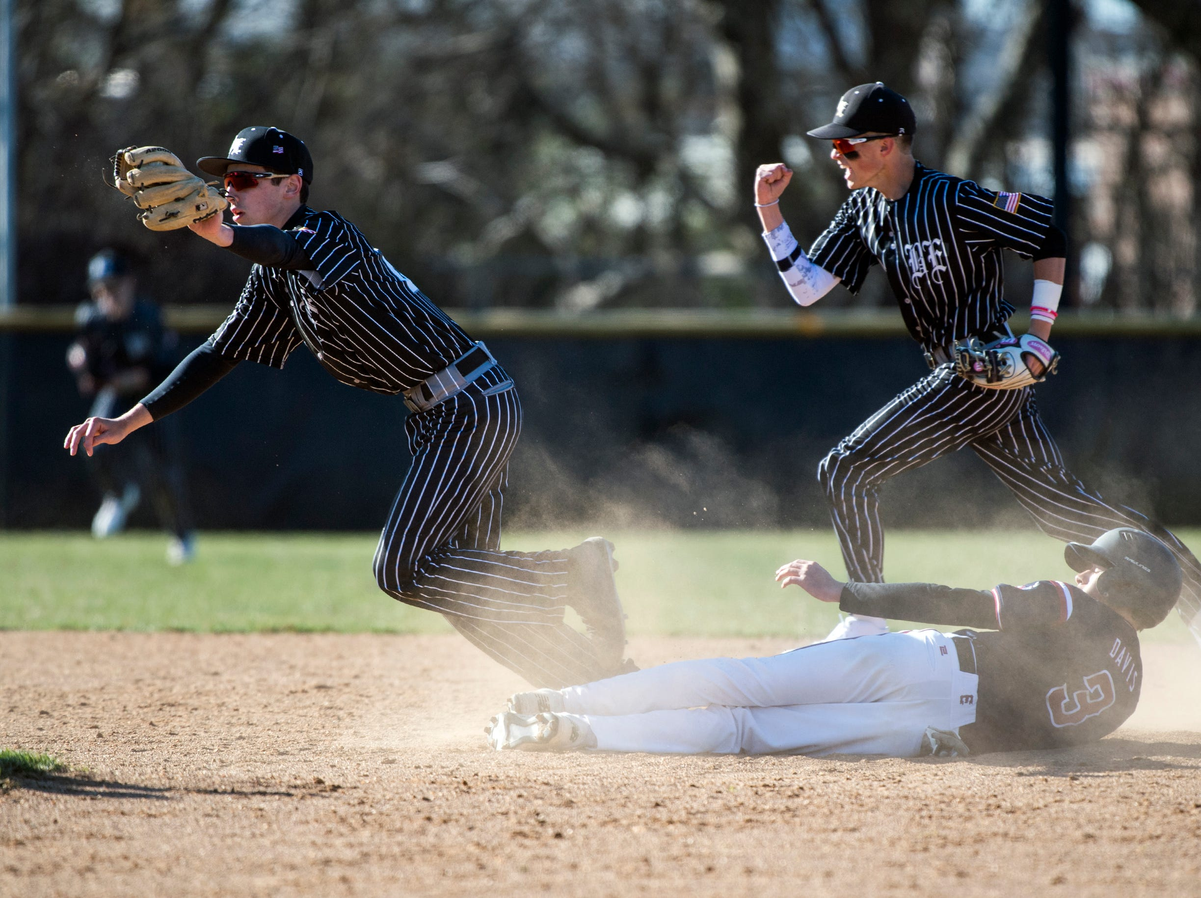Bishop Eustace's Eric Sabato, left, tags out Eastern's Zach Davis (3) Monday, April 1, 2019 in Pennsauken. Eustace won 12-0.