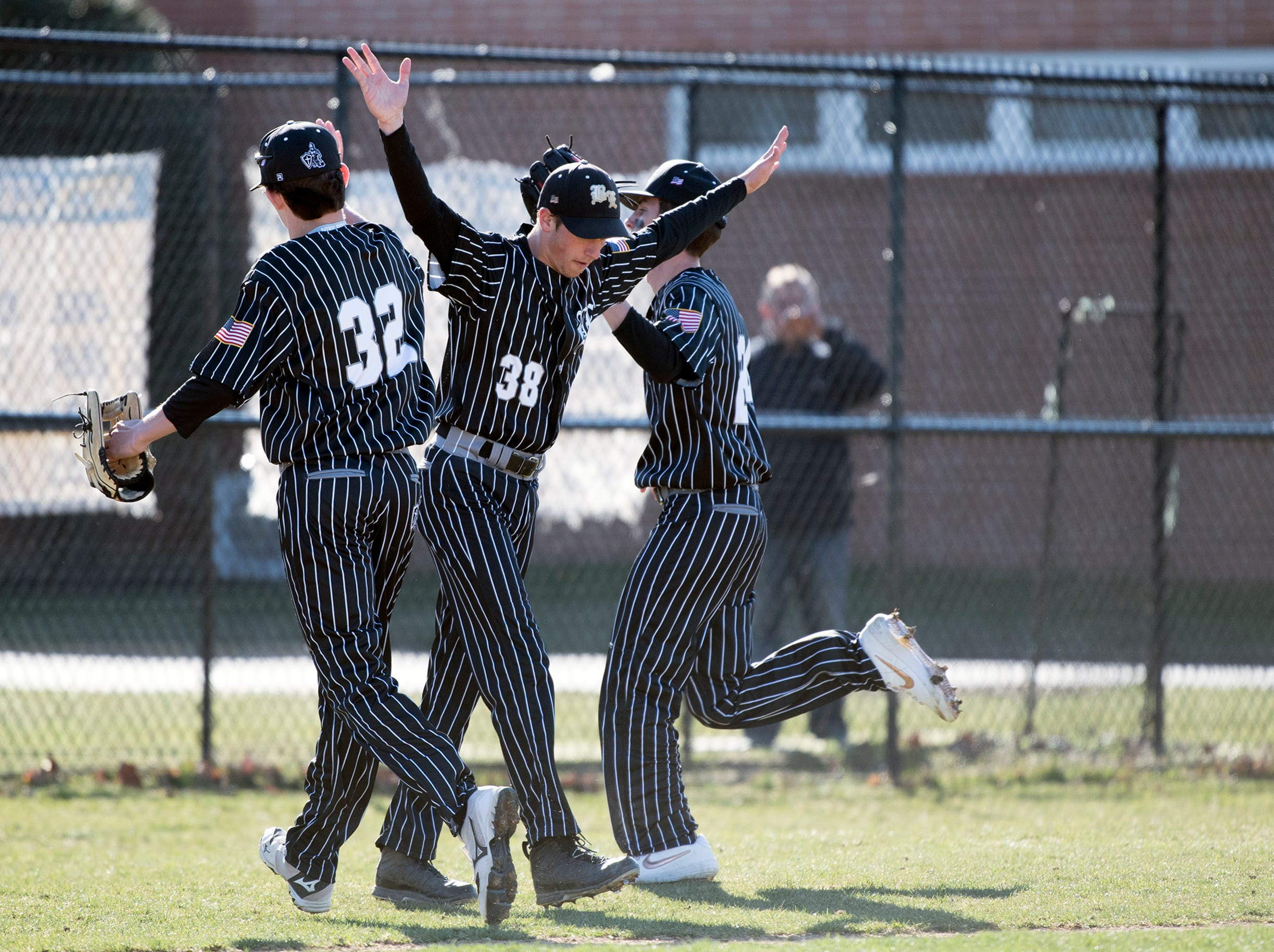 Bishop Eustace's Jake Argentieri (38) high fives teammates in between innings against Eastern Monday, April 1, 2019 in Pennsauken. Eustace won 12-0.