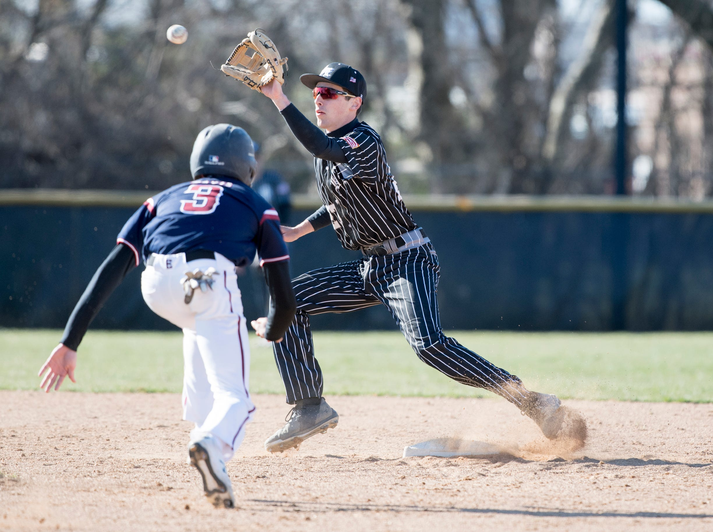 Bishop Eustace's Eric Sabato (27) tags out Eastern's Zach Davis (3) Monday, April 1, 2019 in Pennsauken. Eustace won 12-0.