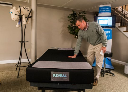 Globe Furniture owner Seth Brown demonstrates a mattress that tests pressure points to help the customer be matched with just the right mattress.