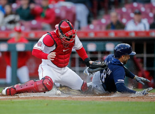 Brewers leftfielder Ryan Braun slides safely ahead of a tag from Reds catcher Tucker Barnhart in the top of the first inning Monday at Great American Ball Park.