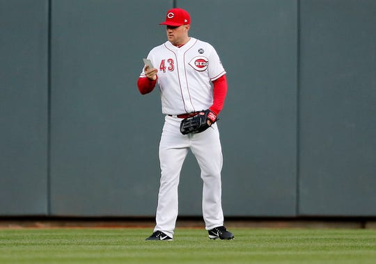 Cincinnati Reds center fielder Scott Schebler (43) looks to a note card for fielding notes between batters in the top of the second inning of the MLB National League game between the Cincinnati Reds and the Milwaukee Brewers at Great American Ball Park in downtown Cincinnati on Monday, April 1, 2019.
