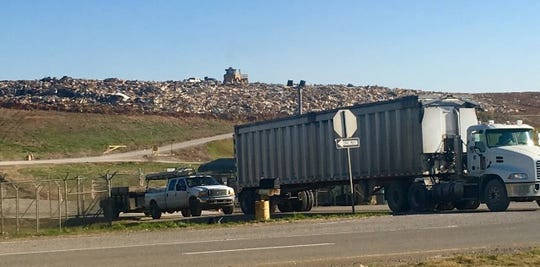 A line of trucks exits the Woodlawn landfill Tuesday morning as the trash piles up behind them.