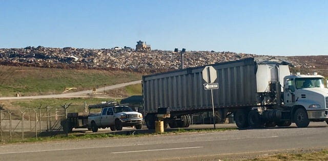Trucks exit the Woodlawn landfill as the trash piles up behind them.