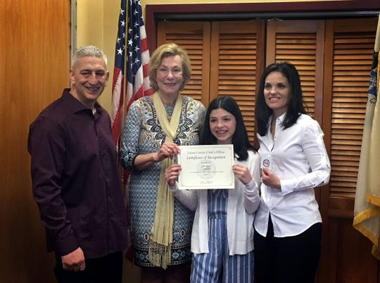 """Union County Clerk Joanne Rajoppi congratulates the winners of the """"I Voted"""" Sticker Design Art Contest sponsored by the Clerk's office. Gina Fabio of the Deerfield School in Mountainside is the winner in the Grade 5 to 8 category. Gina Fabio was joined by her parents Joe and Lisa Fabio."""