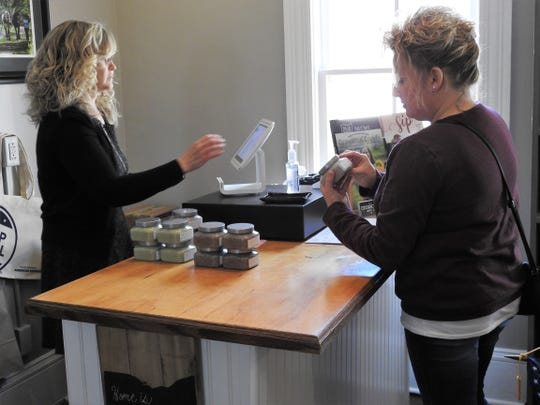 Mindy Brems, executive director of the Coshocton Visitors Bureau, and Donna Maloy who does woodworking through Hickish Home & Hubby, look at some scrubs for sale at the newly renamed Coshocton Supply Company.