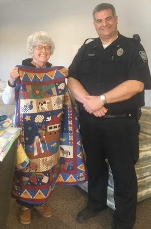 Indianola resident and quilter Connie Phillips donated seven quilts to the Indianola Police Department to help sooth children enduring traumatic times. Officer Chris Marsh accepted the gift.