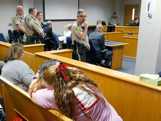 A sheriff's deputy motions for silence as Jennifer Lewis' mother, Sheri McCormick, and godmother, Mary Maxwell-Rockwell, react to the verdict finding Stanley Carter Liggins guilty in Jennifer's death on Tuesday April 2, 2019 in Waterloo, Iowa. In his fourth trial, a jury found Liggins guilty in the 1990 killing of the 9-year-old girl whose body was found in Davenport.