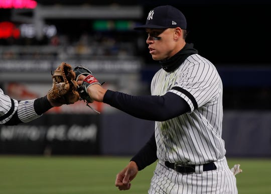 Aaron Judge is congratulated by a teammate at the end of the top of the eighth inning, after he made a diving catch on a line drive with two runners on base Monday.