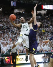 Michigan State guard Cassius Winston scores against Michigan forward Colin Castelton during second half action Saturday, March 9, 2019 at the Breslin Center in East Lansing, Mich.