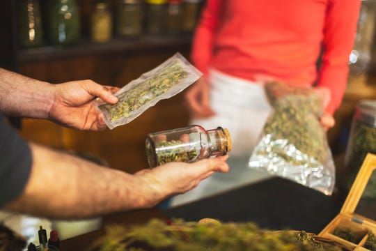 Man buying cannabis buds at small cannabis store.
