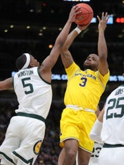Michigan State guard Cassius Winston blocks a shot by Michigan guard Zavier Simpson during first half action of the Big Ten Tournament Championship Sunday, March17, 2019 at the United Center in Chicago, Ill.