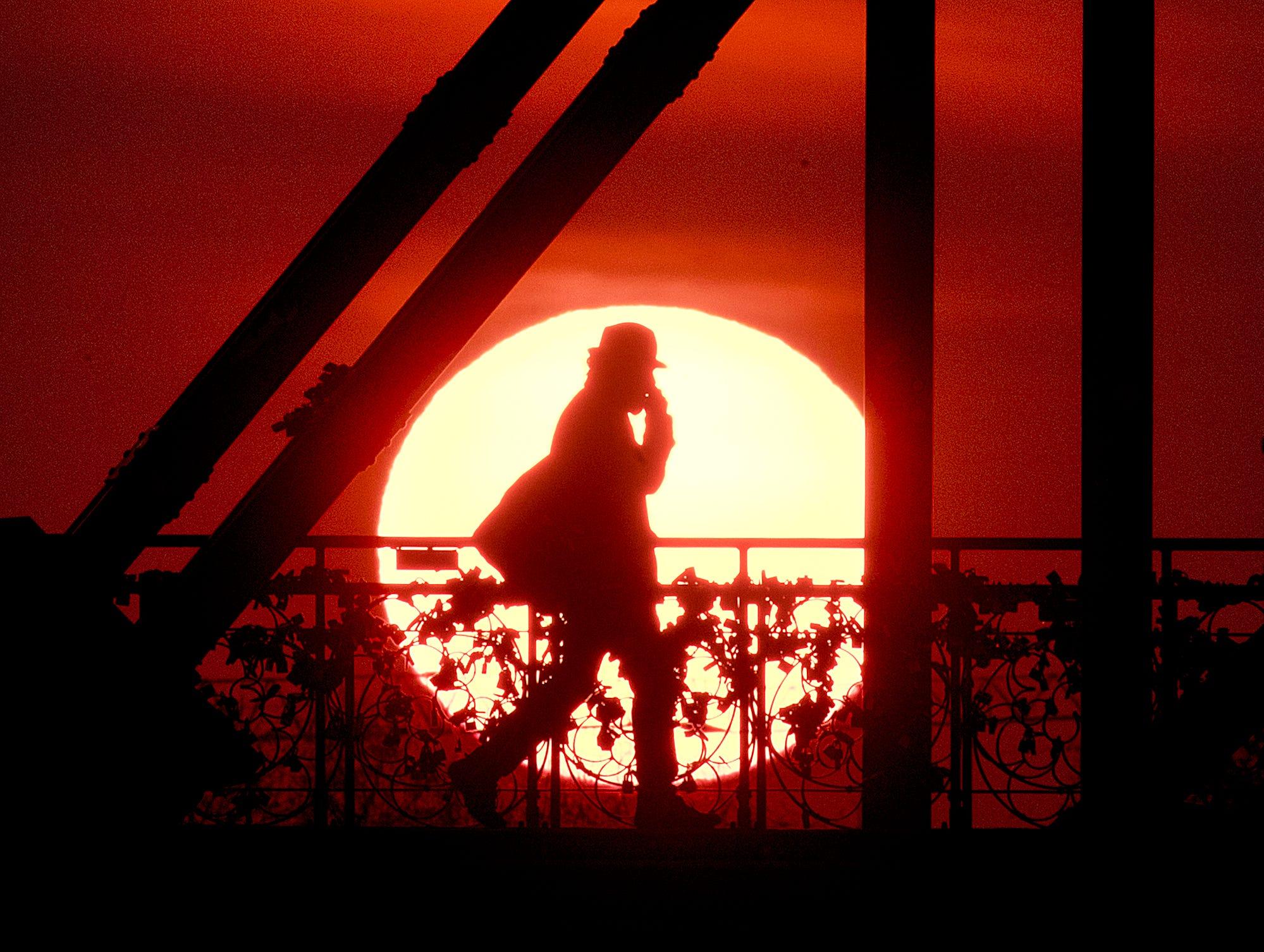 "The sun rises behind the ""Eiserne Steg"" (Iron Footbridge) pedestrian bridge in Frankfurt, Germany, early Tuesday, April 2, 2019."