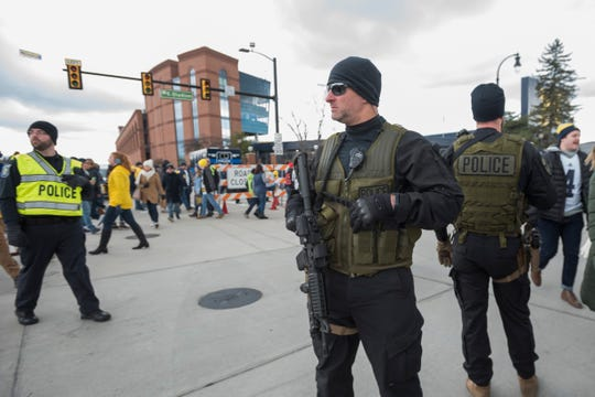 Police monitor the crowd outside of Michigan Stadium before a football game against Ohio State University in Ann Arbor, November 25, 2017.