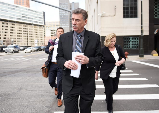 Norwood Jewell, center, leaves the U.S. courthouse  in Detroit after pleading guilty to breaking federal labor laws.