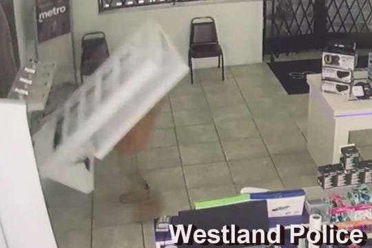 A man is shown on video entering a store and stealing multiple cellphones. In one instance, he attemps to pull a phone off its security tether, causing the display to fall on top of him.