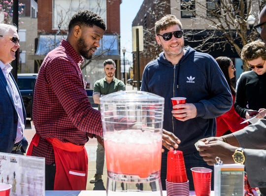 "Courtney Johnson, center left, serves pink lemonade to Sam Stevens, center right, during the YWCA's annual ""Sour Truth"" lemonade stand fundraiser set up outside of Zuki Japanese Hibachi Grill on Main Street in downtown Evansville, Ind., Tuesday, April 2, 2019. Men were charged a dollar and women were charged 75 cents for their lemonade to call attention to the gender gap in wage earnings on Equal Pay Day."